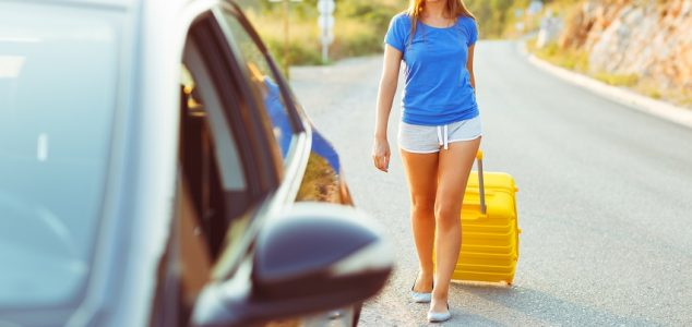 Young woman with a yellow suitcase goes to a car